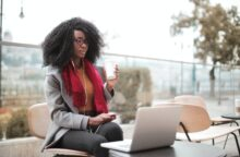 A young Black woman sits outside on her laptop, drinking a coffee and looking up how to protect her credit score from COVID.