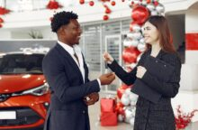 A smiling woman hands a man the keys to a car he just successfully leased